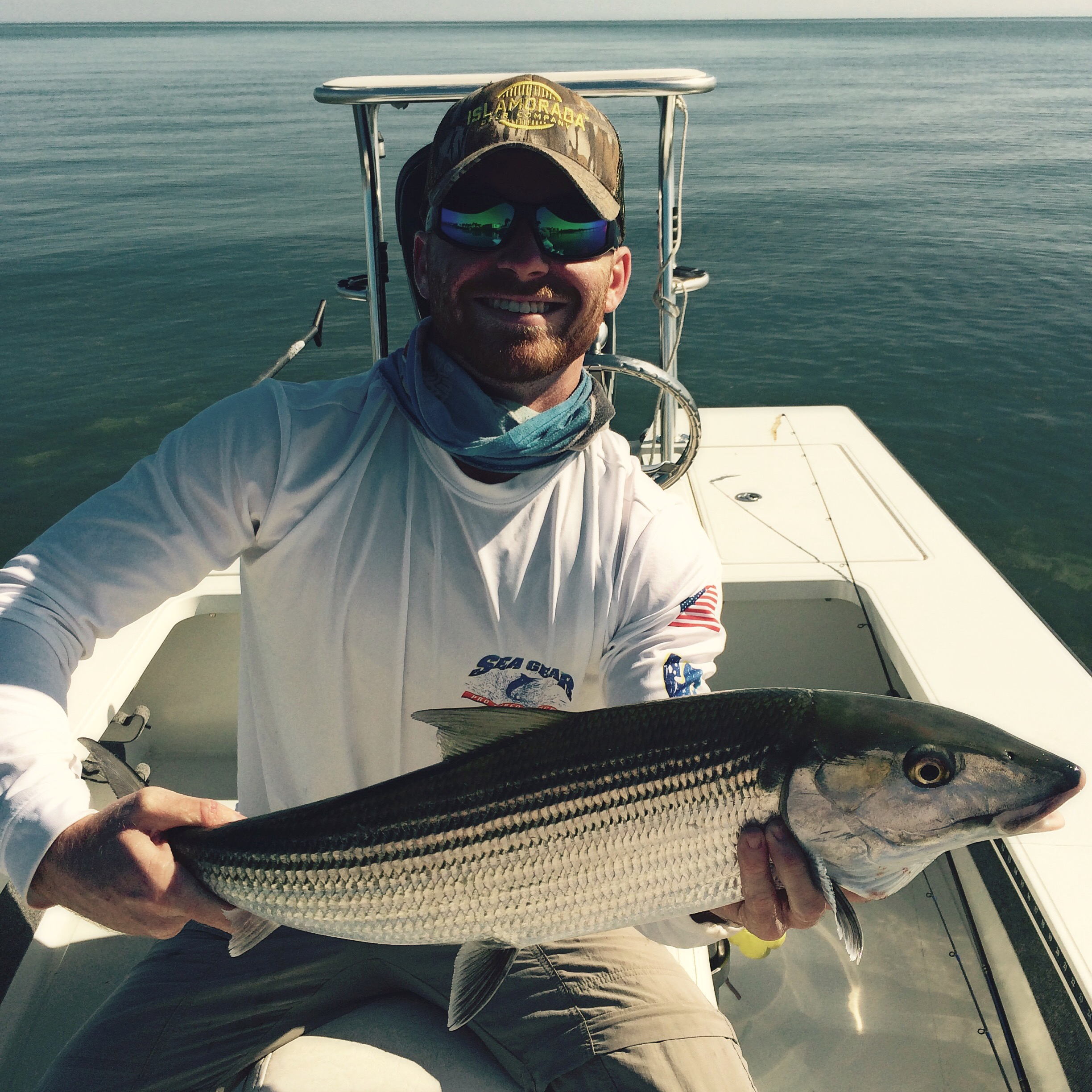 Smiling man holding a caught bonefish. Opens a photo gallery.