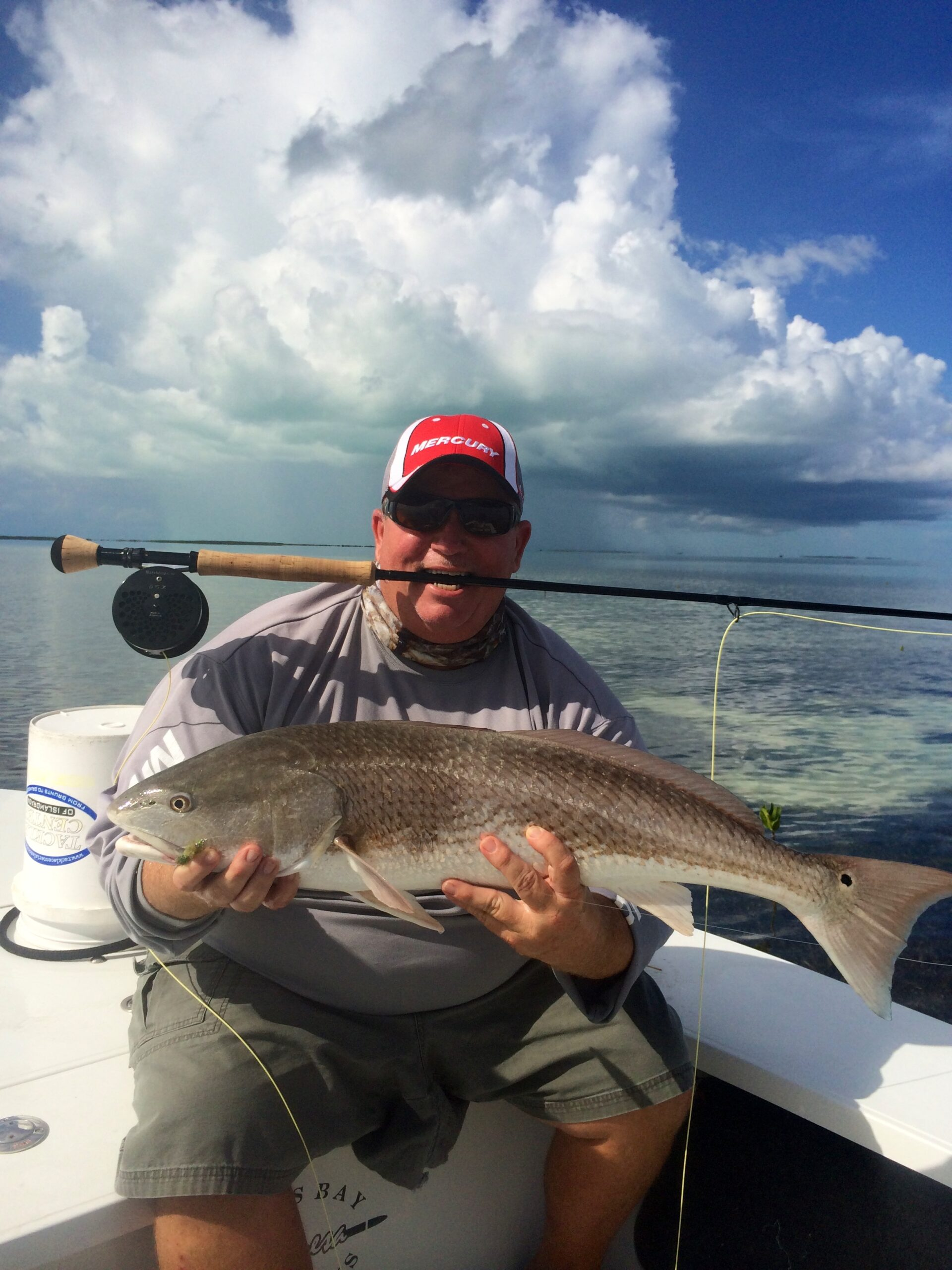 Funny man with fly rod in mouth holding a Redfish. Opens a photo gallery.