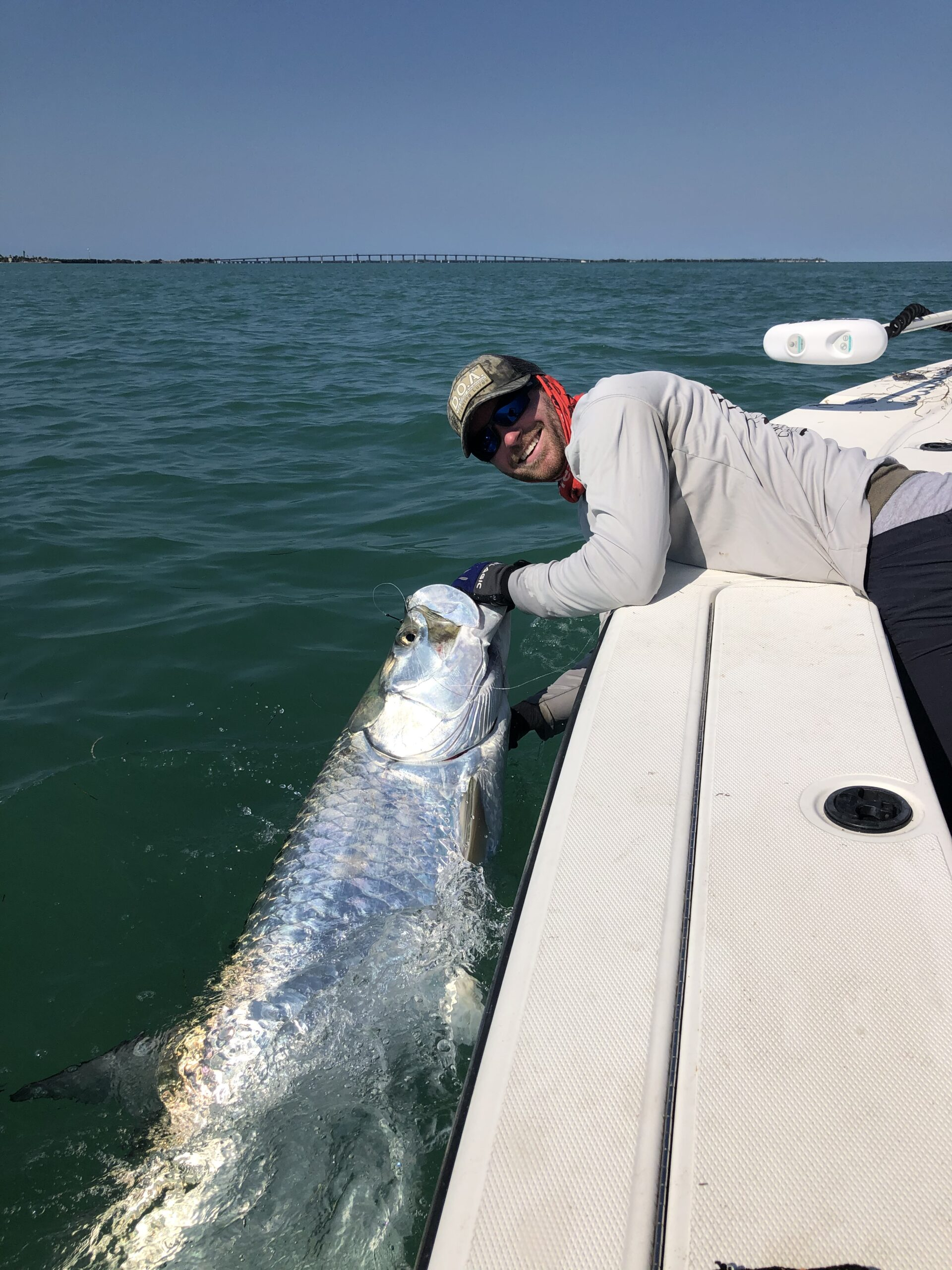 Smiling man and Tarpon at the boat. Opens a photo gallery.