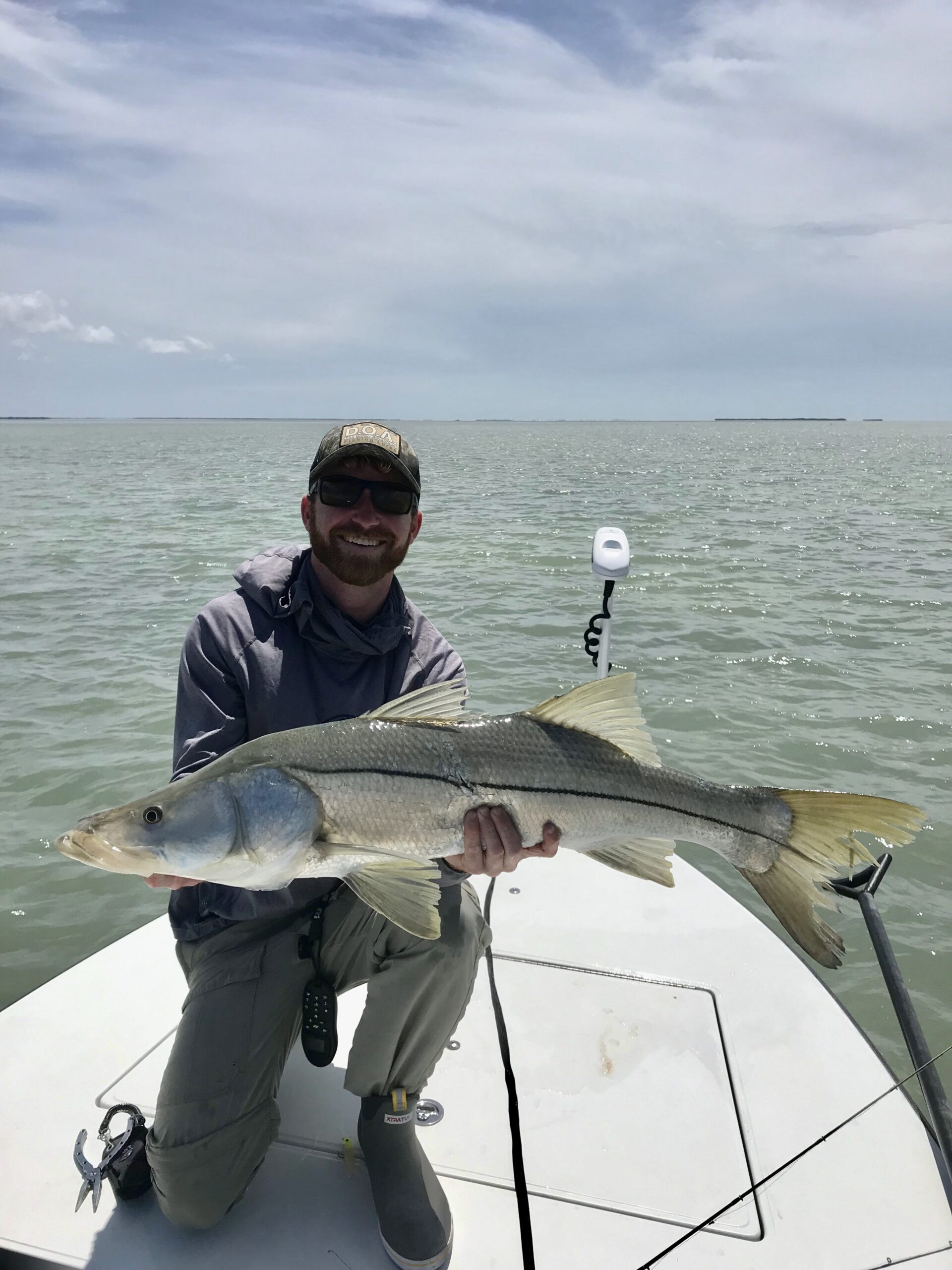 Smiling man holding a big snook. Opens a photo gallery.